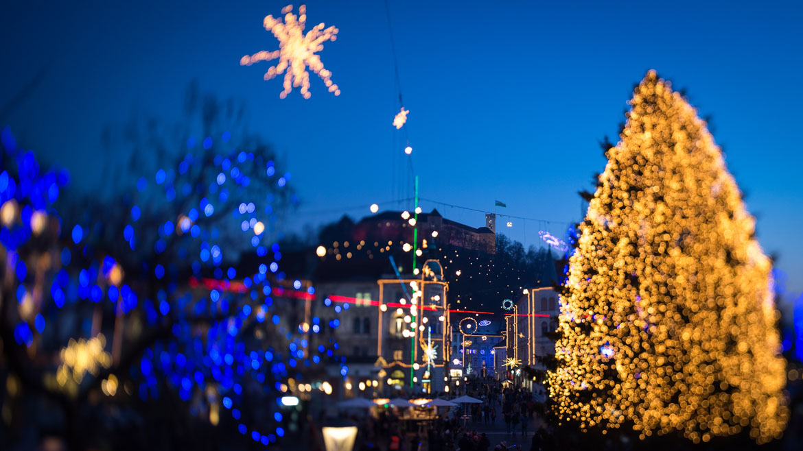 This picture taken with a tilt and shift lens shows people walking in the centre of Ljubljana as it is illuminated with Christmas decorations on December 6, 2013.   AFP PHOTO / JURE MAKOVEC