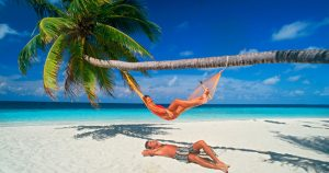 Couple chilling out with hammock under palm trees and sunny skies on white sandy beach in Maldives